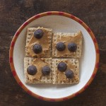 Four Triscuits arranged on a small plate. Each is spread with creamy peanut butter and has two chocolate chips pressed into