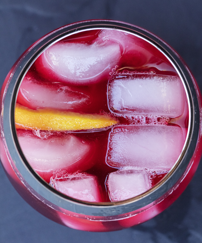 hibiscus aqua fresca in a glass with ice and a orange slice