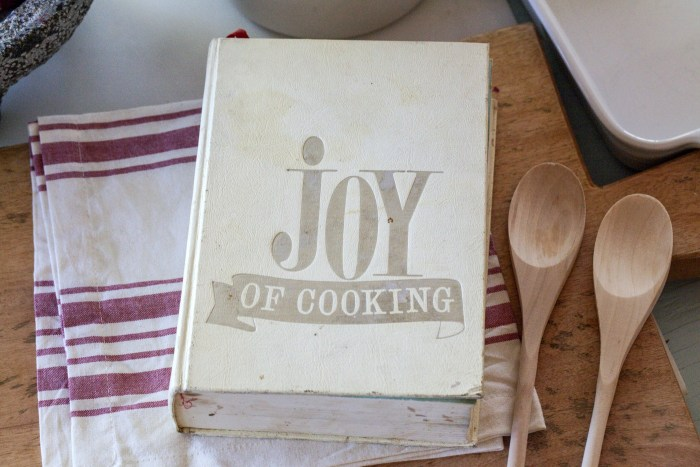 Vintage edition of Joy of Cooking on a kitchen table with wooden spoons