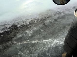 There is no berm in this portion of the road and you can see the top layer of ice with water flowing underneath it.