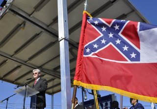 Gov. Phil Bryant spoke at the groundbreaking of Mississippi's new Civil Rights Museum next to the state flag containing the Confederate battle symbol. Myrlie Evers-Williams, the widow of slain Jackson civil-rights hero Medgar Evers, is visible below the flow.
