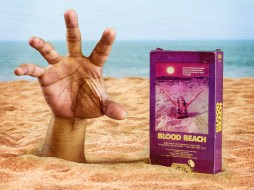 """""""Blood Beach"""" VHS box cover sitting in the sand next to a hand of someone being dragged beneath the surface."""