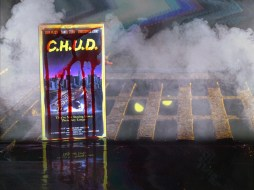 """Blood dripping """"C.H.U.D."""" VHS box cover upon a foggy sewer grate with a creature's glowing eyes."""