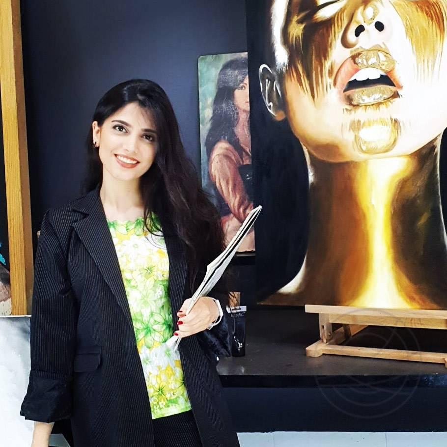 Niloofar Mahafel standing next to her painting Golden