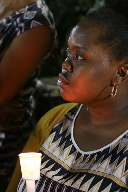 A woman holds a candle at a prayer vigil for Walter Scott.