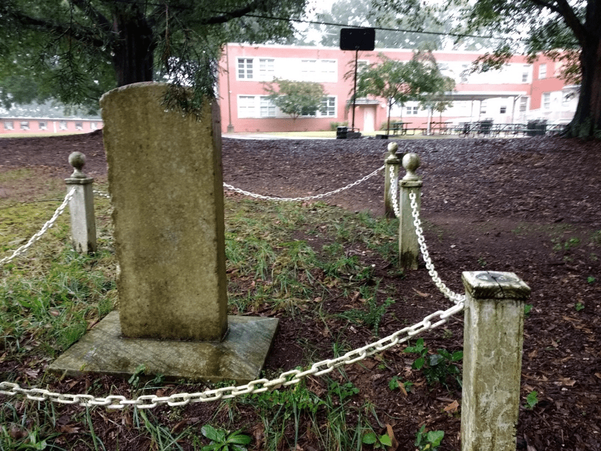 Rear of marker for Theophilus Hunter's grave installed in 1940 by the Daughters of the American Revolution. (School in distance)
