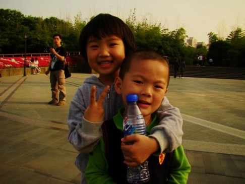 Hey, that's not the 'Peace' sign. Shanghai's next top model hamming it up with her brother in the park...shoving bottle in his face...