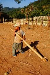 Young boy playing with his big wood stick