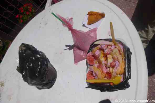 Other prepared products from the market juice in it plastic bag with a straw, fruit salad and empanada