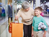 Portrait of cute child looking at shop window with his grandmother holding paperbags near by