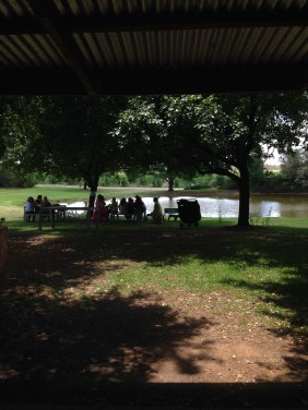 People enjoying a cheese platter near the lake