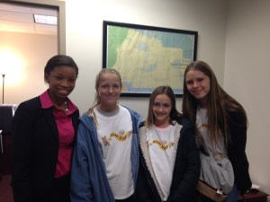 Kidz with aide in Senator Simmon's Office, delivering their workbook.