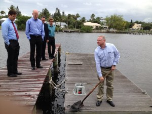 Photo of Stuart News article where Kevin Powers of the SFWMD shows Gov. Rick Scott some muck that is located at the end of Power's dock in Stuart. 2014. (Photo Stuart News)