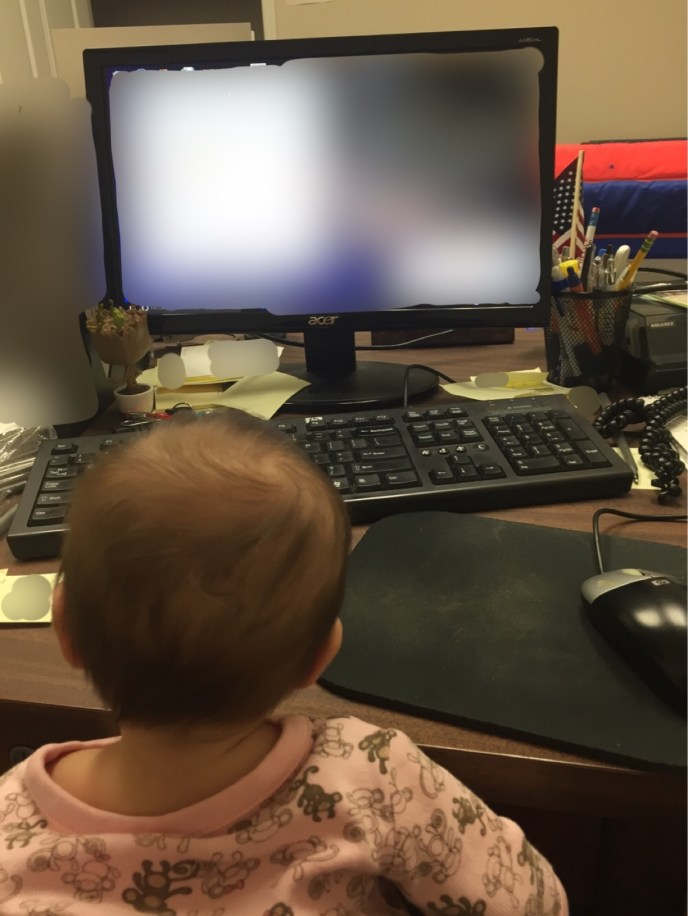 Baby sits at a desk in front of a computer