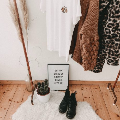 boots and some clothes on a rail, next to a plan and a board with a motivational quote on it