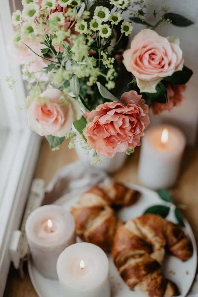 Pale pink flowers resting on a wooden table, with lit candles and two Croissants on a white plate