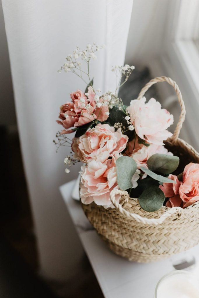 A basket of pale pink and white flowers, sat on a white table with a sheer white curtain in the background