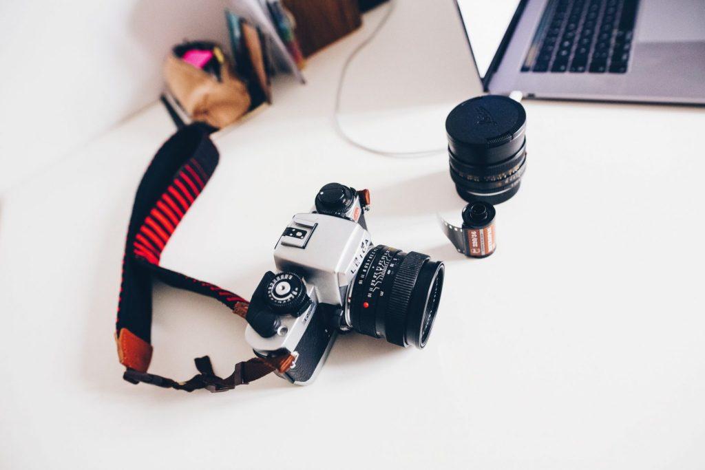 Leica camera + etra lens on a white desk