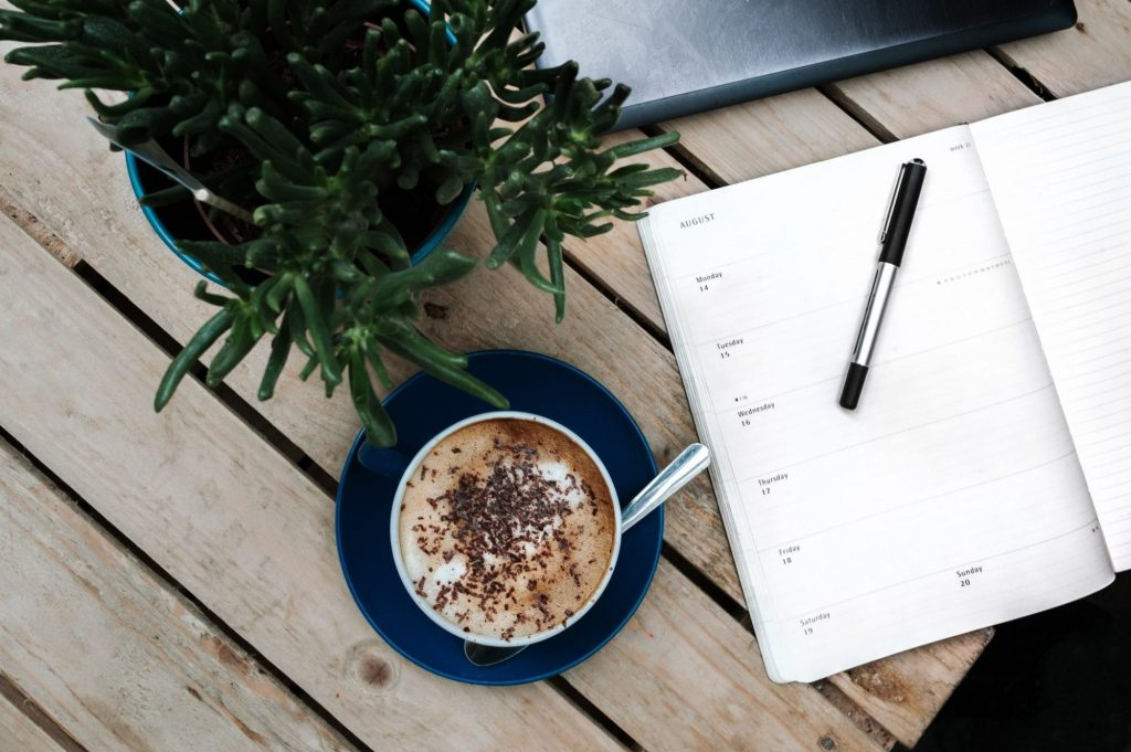 cup of coffee with sprinkles on top next to an open diary/planner and a plant. all resting on top of a wooden table