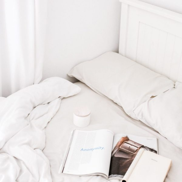 a messy bed with white sheets, with a cup of tea on it and a few magazines