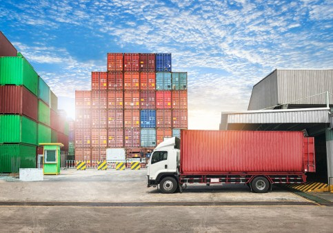 Cargo transportation unloading container trucks in warehouse logistics import export background