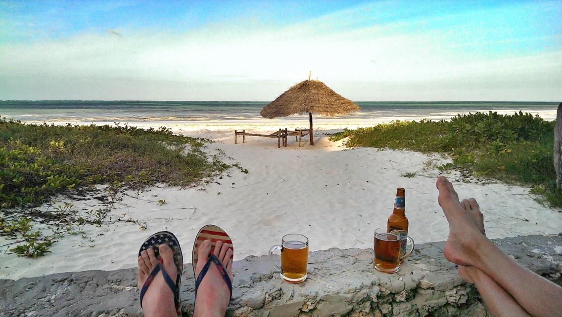 Relaxed den Sonnenuntergang am fast verlassene Strand genießen