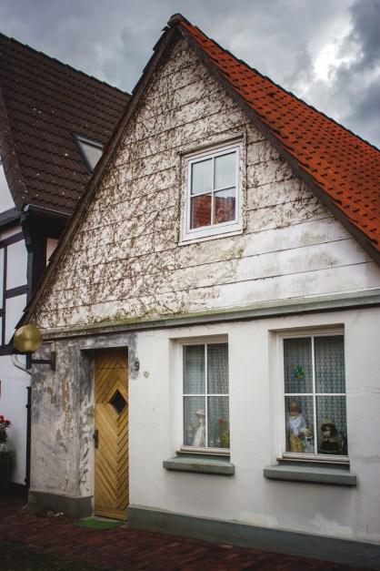 Casa en Nienburg con algunos muñecos en las ventanas como si de un escaparate se tratara.