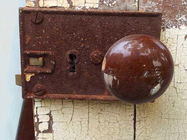 rusty keyhole on peeling white painted door