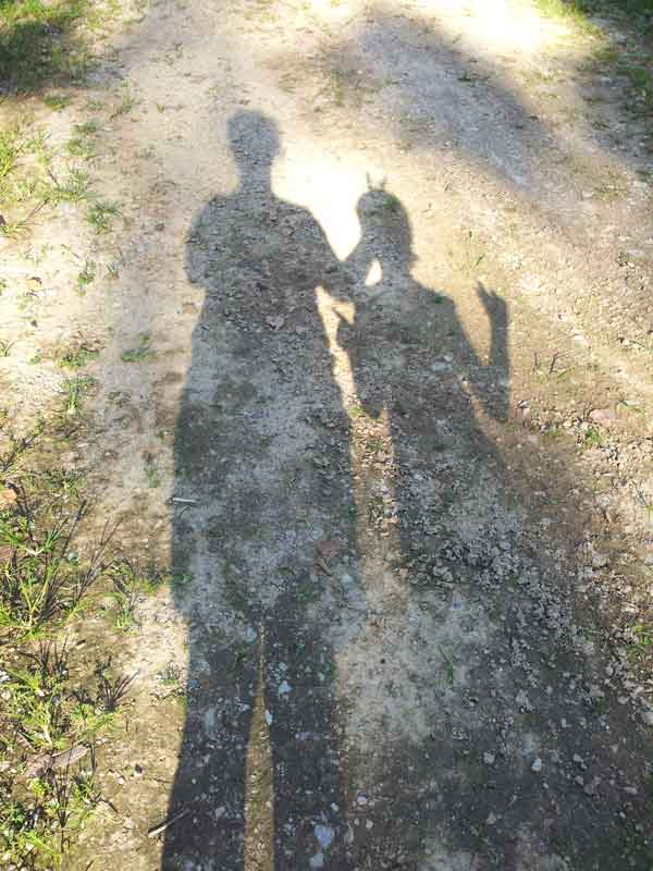 shadows of two figures waving