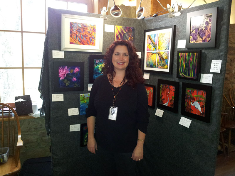 Jaime Haney standing next to her original paintings during the 2014 Christmas in New Harmony