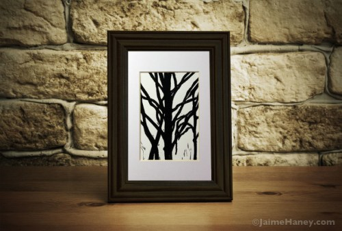black tree mono-print with white mat shown in black frame on desk