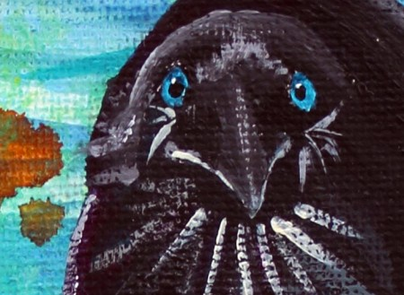 close up of painted crow face with blue eyes