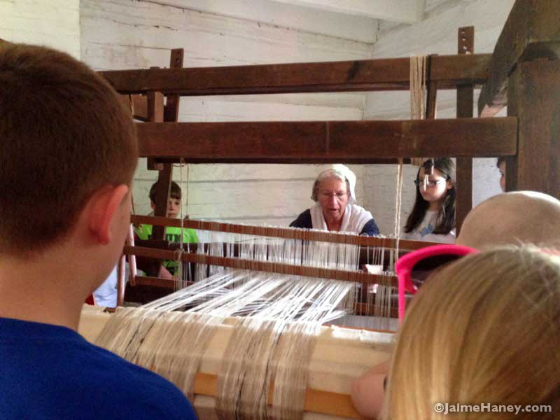 Peggy Taylor demonstrating on old wooden loom during Heritage Artisans Days in New Harmony Indiana 2016