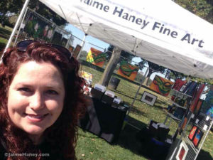 Jaime Haney at art booth at Audubon Mill park in Henderson, Kentucky giving Artisan Market review