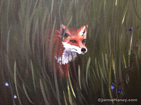 a fox hiding in the weeds