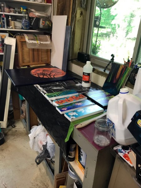 Paintings drying on work table after being varnished.