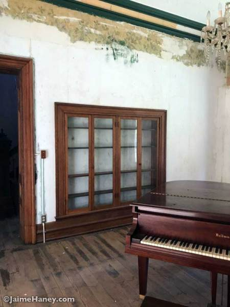 Parlor with piano and built in cabinetry