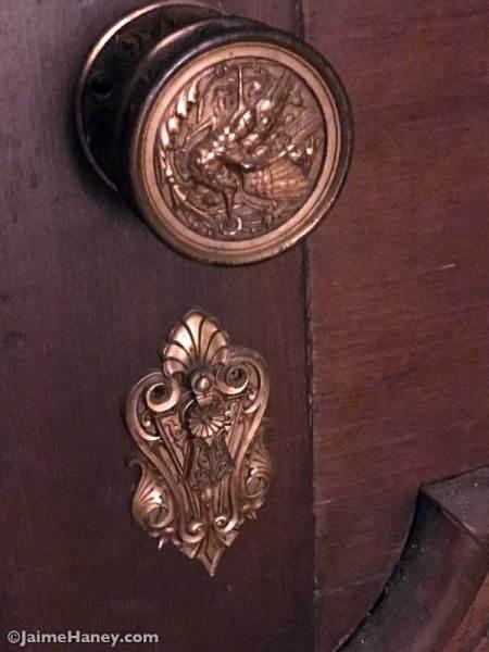 brass door knob decorated with bird