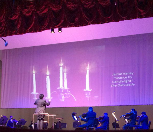 "My painting ""Seance by Candlelight"" shown on screen above the orchestra"