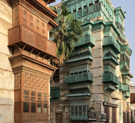 Street view of Jeddah AlBalad in Saudi Arabia with turquoise and brown mashrabiyah facades with a palm tree