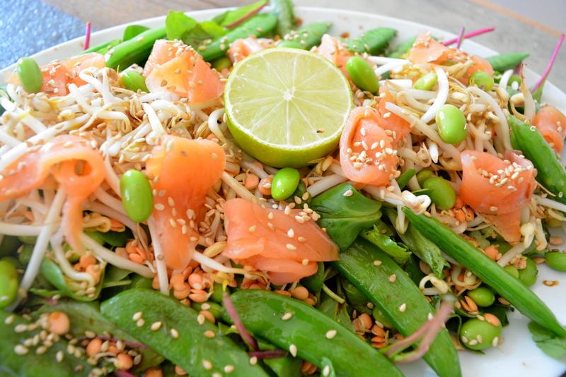 Aziatische salade met gerookte zalm, taugé, sugarsnaps, endame, limoen, linzenkiemen, snijbiet en wasabi rucola