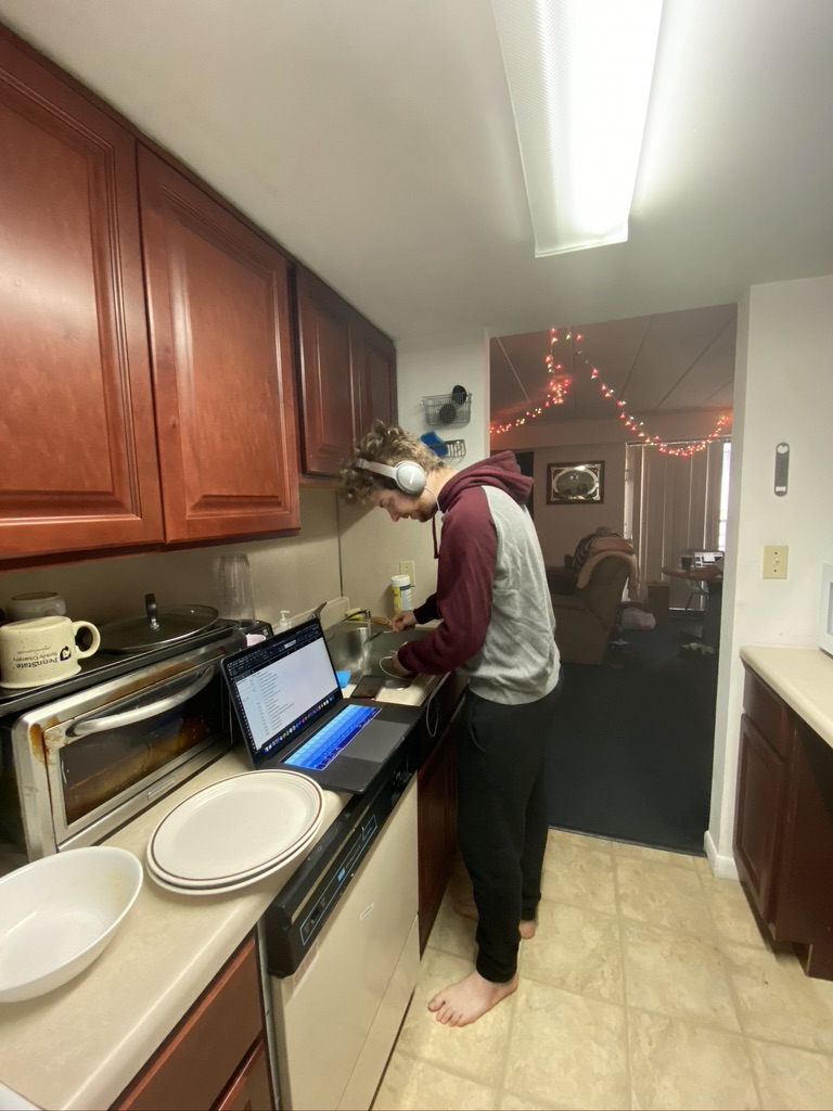 A person stands in a kitchen  Description automatically generated with low confidence