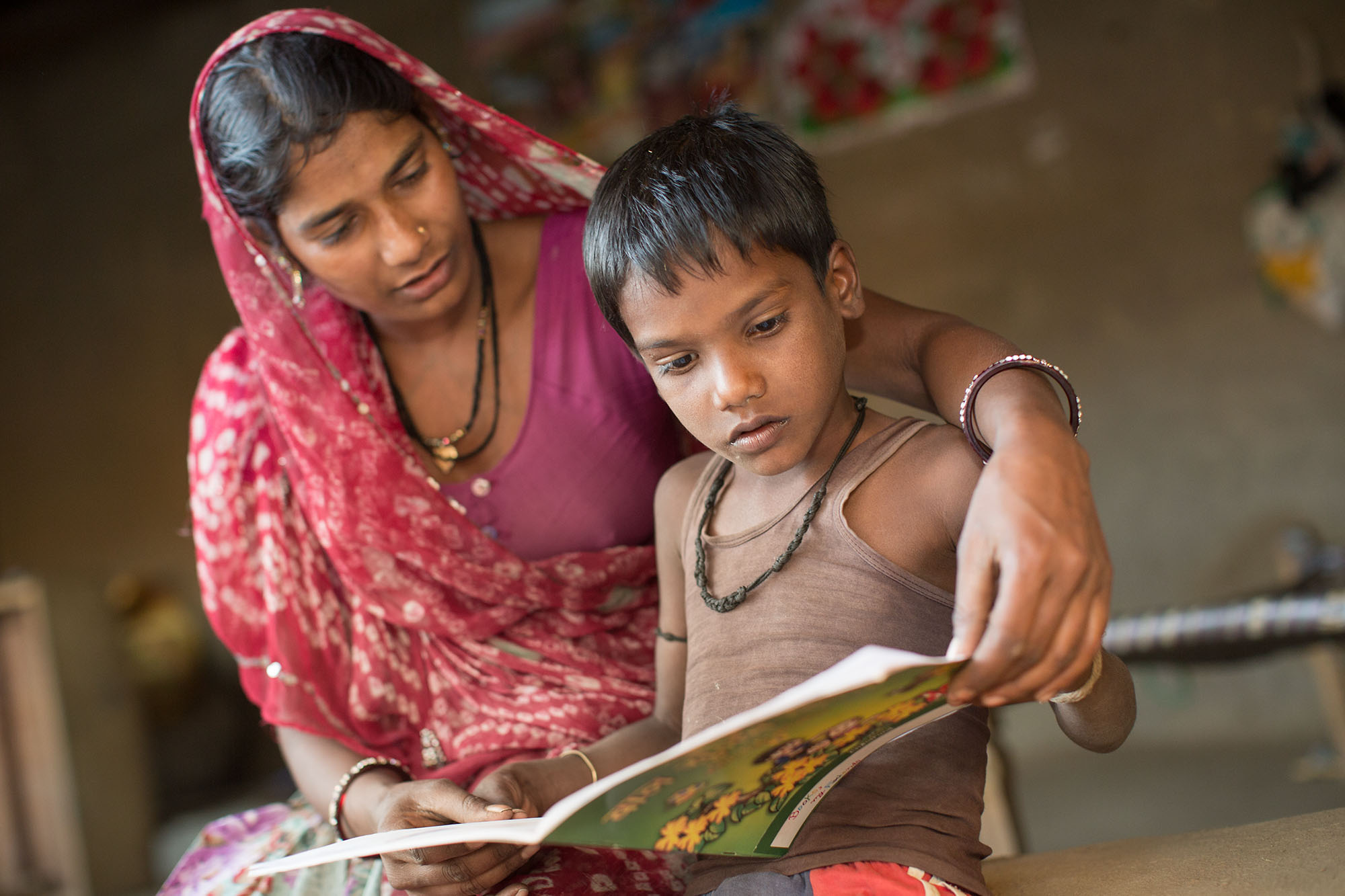 A mother reads to her son in Udaipur, India.