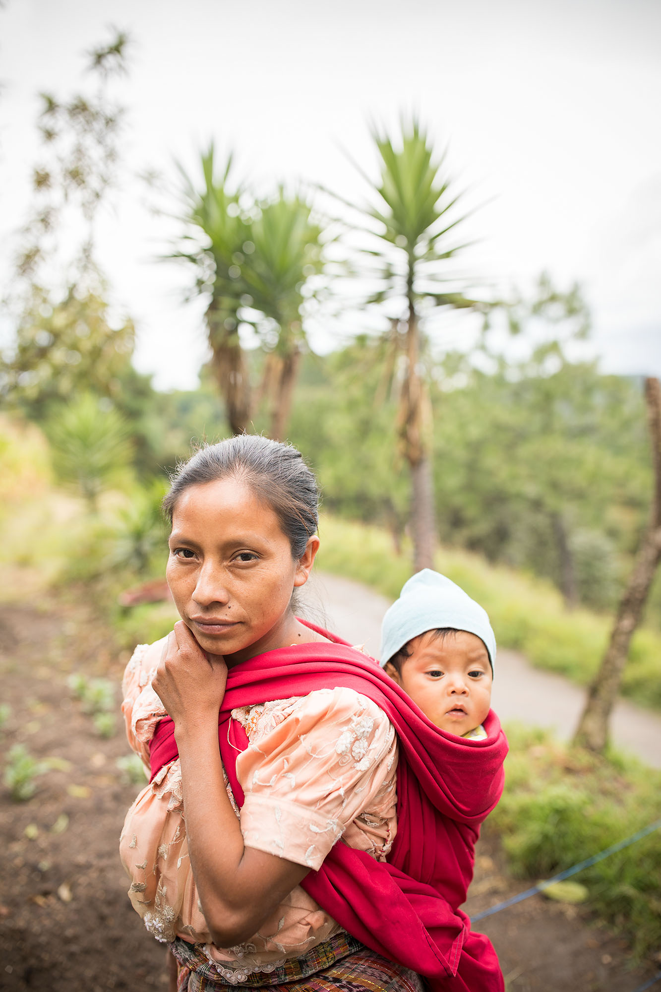 A mother carries her son on her back in the highlands of Guatemala.