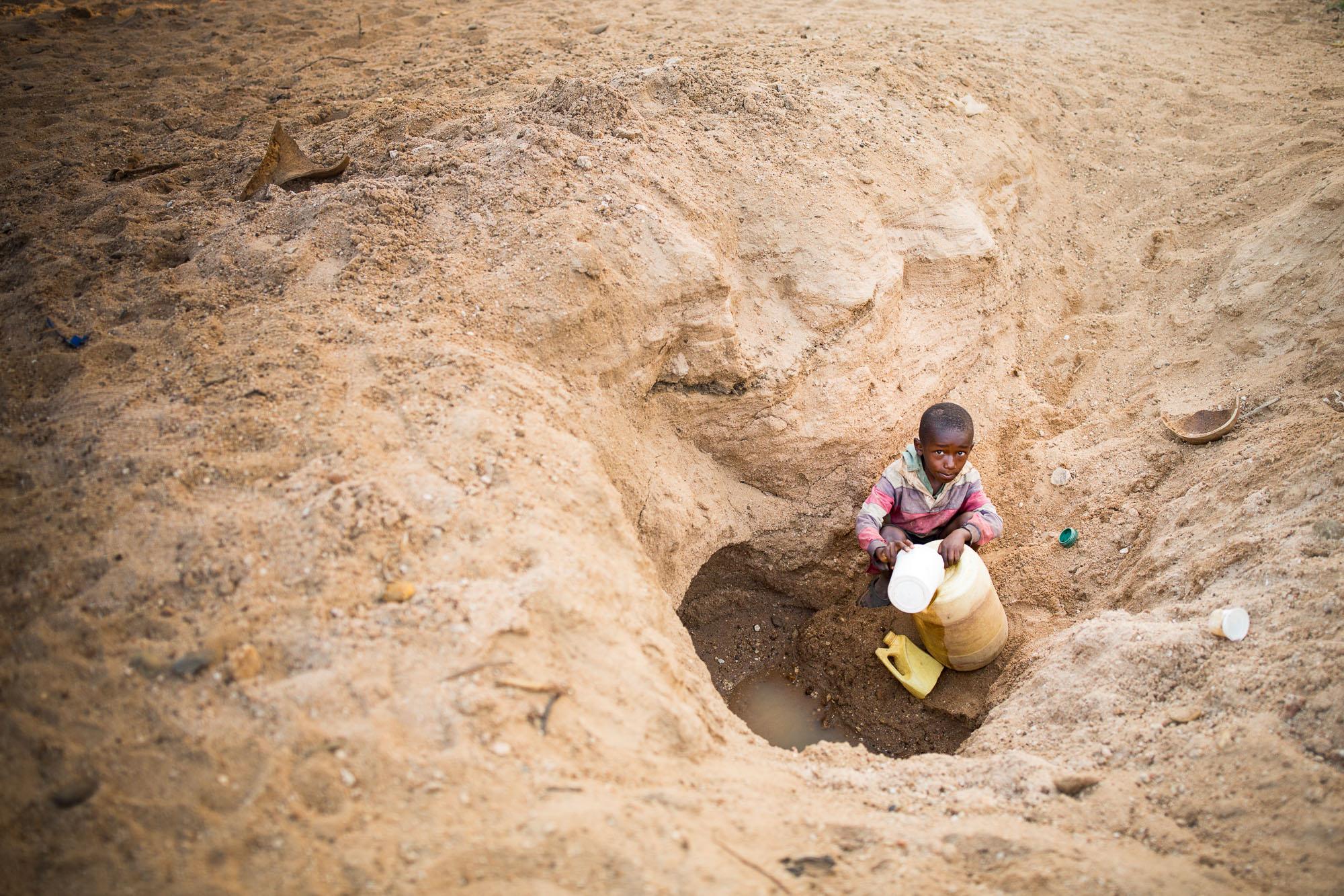 Mwangela (8) digs for water in a dry riverbed in Makueni County, Kenya.