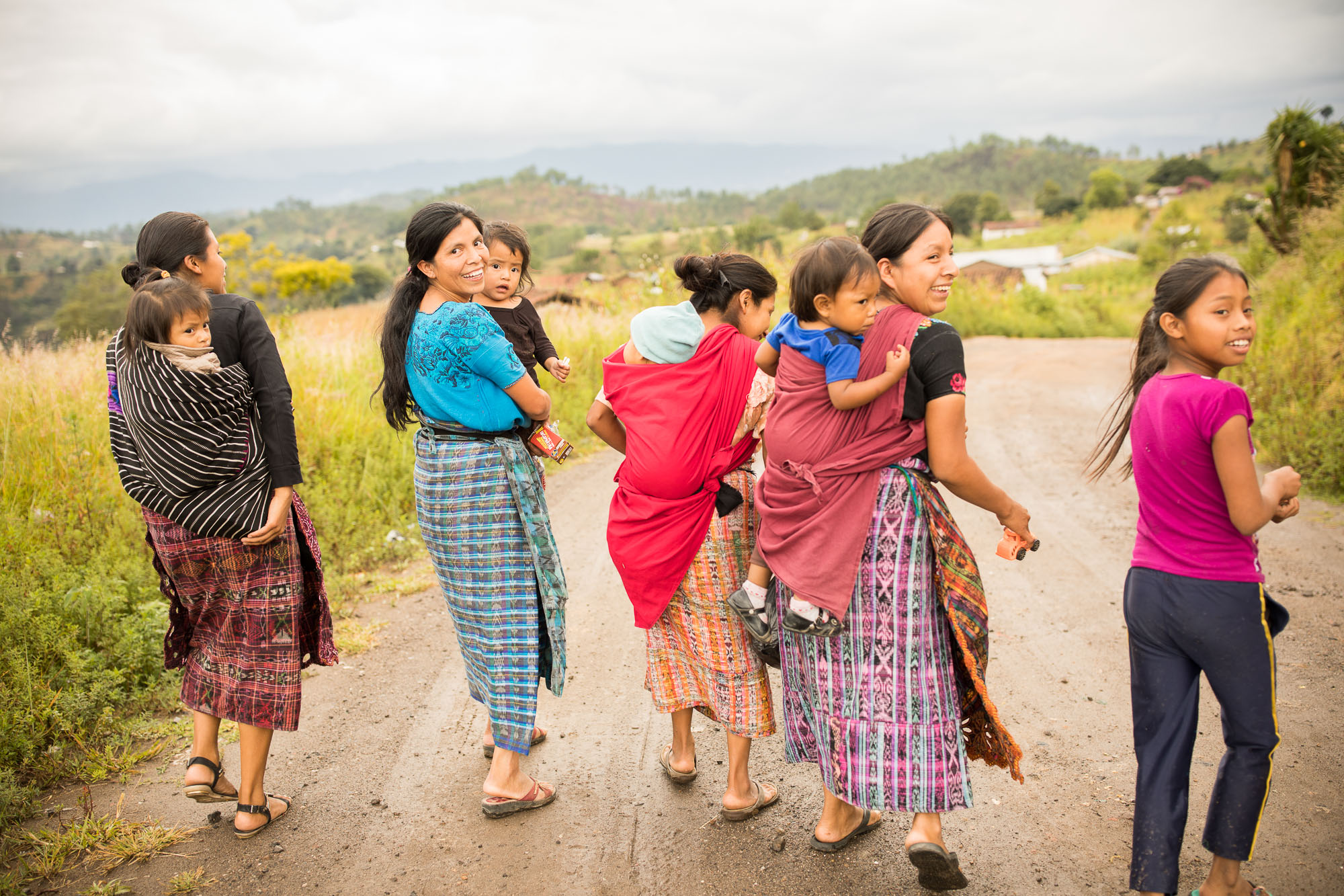 Mothers walk along a rural road with their children in Totonicapán Department, Guatemala.