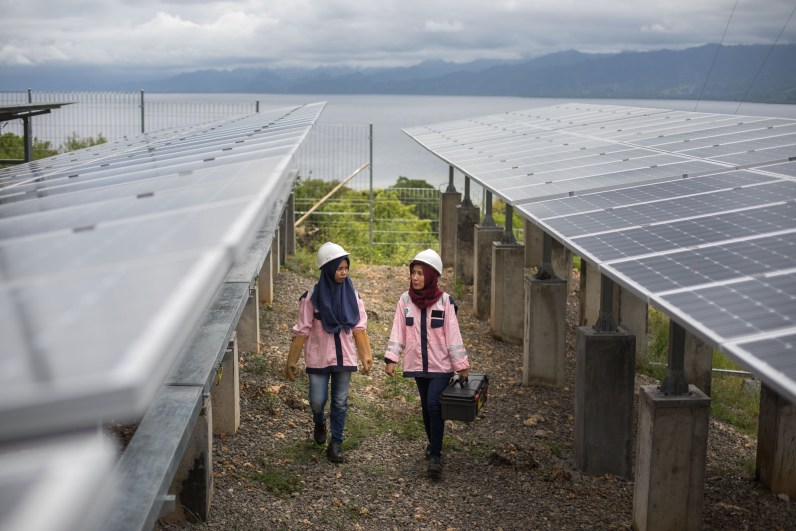 Electrical technicians inspect solar panels on Karampuang Island, Indonesia.