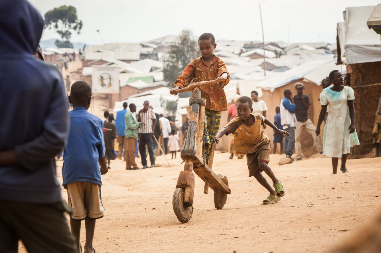 Children from the Democratic Republic of Congo play on a homemade scooter on the streets of a refugee camp in Rwanda.