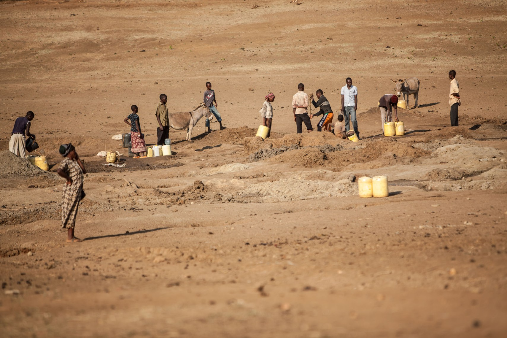 Residents dig in a dry riverbed to access water in Migwani, Kenya.