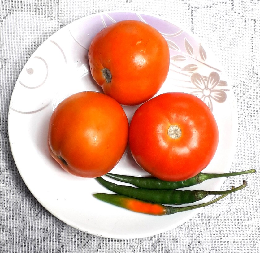 tomatoes and chilies are kept on a plate